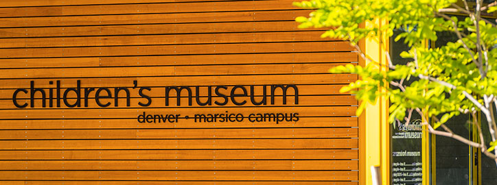 Children's Museum of Denver, Marsico Campus sign on wood slat wall with a tree in the foreground